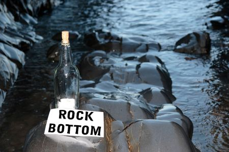 rock bottom: a bottle with a message on being at rock bottom standing on a rocky coastline