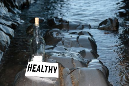 castaway: a bottle with a message on water is healthy standing on a rocky coastline