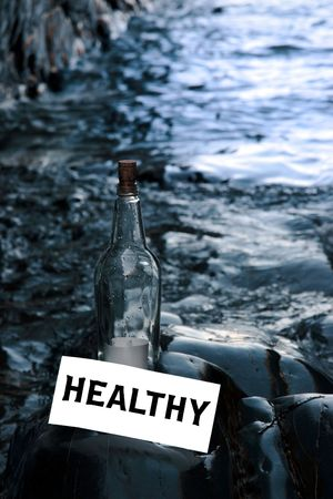 a bottle with a message on water is healthy standing on a rocky coastline photo