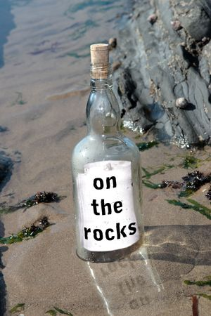 a bottle with a message on being on the rocks standing on a rocky coastline photo