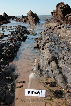 castaway: a bottle with an email message label standing on a rocky coastline Stock Photo