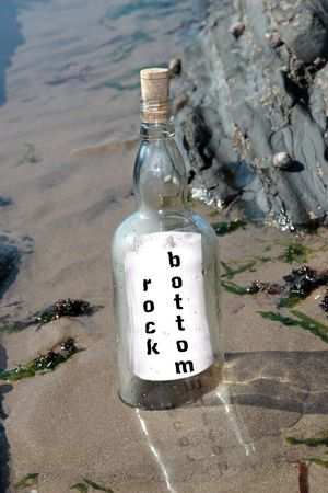 rock bottom: a bottle with a concept message on being at rock bottom standing on a rocky coastline Stock Photo