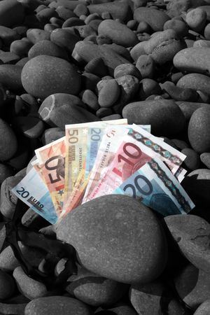 colorful european money on a rocky beach depicting holiday money with background in black and white. photo