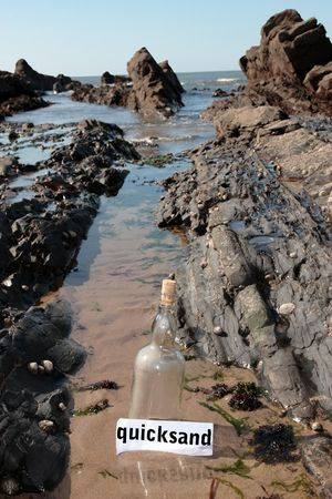 quicksand: a bottle with a quicksand message label sinking on a rocky coastline