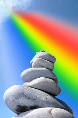 balance concept: rocks balanced on a calm spiritual beach on the coast of ireland with the energy of a  rainbow coming from the clouds Stock Photo