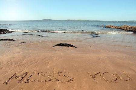 miss you inscribed on the beach with waves in the background on a hot sunny day photo
