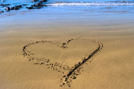 a romantic love heart inscribed on the beach with waves in the background on a hot sunny day Stock Photo - 5892548