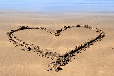 a romantic love heart inscribed on the beach with waves in the background on a hot sunny day