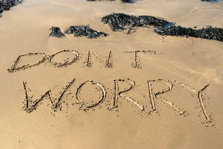 dont worry: dont worry inscribed on the beach with waves in the background on a hot sunny day