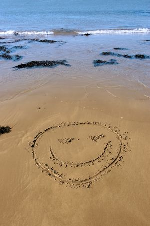 a smiley face icon inscribed on the beach with waves in the background on a hot sunny day photo