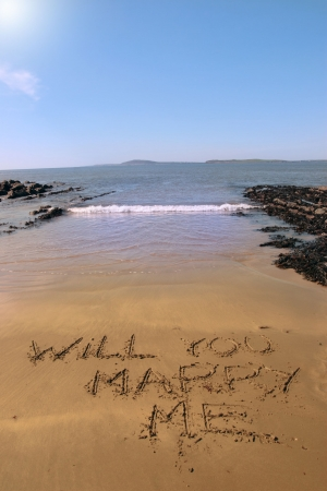a romantic proposal of will you marry me inscribed on the beach with waves in the background on a hot sunny day photo