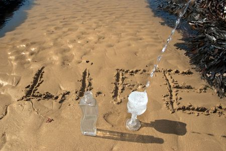 the word life inscribed on the beach with water pouring into the glass showing the concept of living life to the full photo