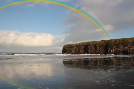 co  kerry: a view of the beach cliffs in ballybunion co kerry ireland with rainbow reflection on a wet stormy day