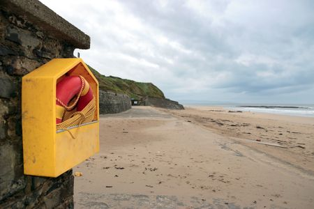 a rescue buoy at ballybunion beach in ireland on a cold deserted winters day photo