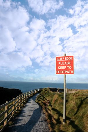 steep cliffs sign: a warning sign of danger at a slippery cliff edge walk Stock Photo