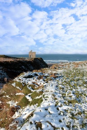 snow covered view of atlantic ocean and castle in ballybunion on a frosty snow covered winters day photo