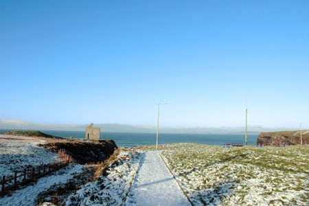 snow covered view of atlantic ocean and castle in ballybunion on a frosty winters day photo