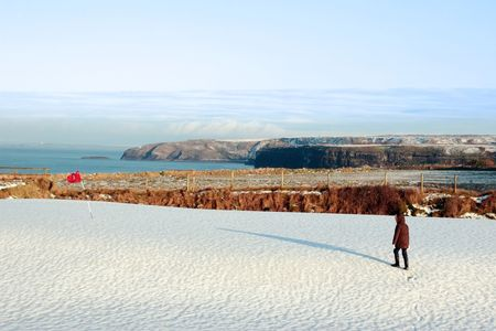 child on a snow covered golf course in ireland in winter with sea and cliffs in background photo