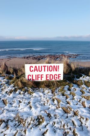 steep cliffs sign: a red caution sign on a cliff edge in snow covered ballybunion