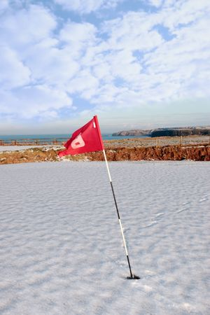 flag on a snow covered golf course in ireland in winter with sea and cliffs in background photo