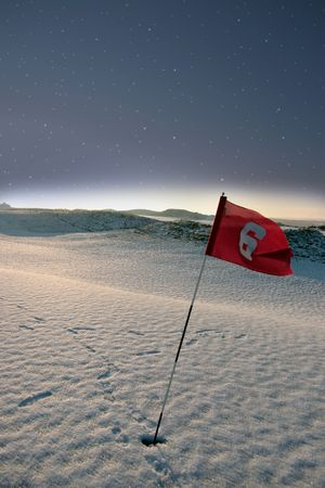 flag on a snow covered links golf course at night in ireland in winter photo