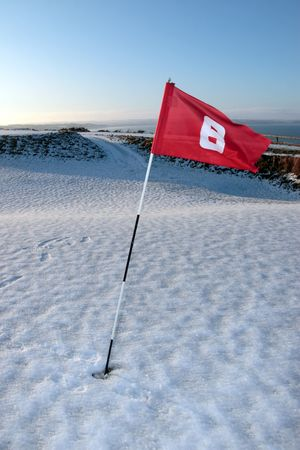 flag on a snow covered links golf course in ireland in winter photo