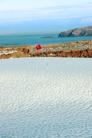 snow covering on a golf course in ireland in winter with sea and cliffs in background photo