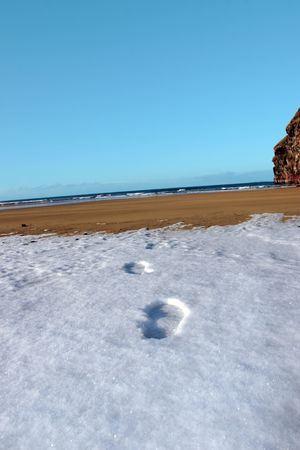 footprints on an empty beach with cliffs on a cold winters day photo