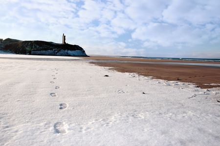 footprints on an empty beach with castle in background on a cold winters day photo