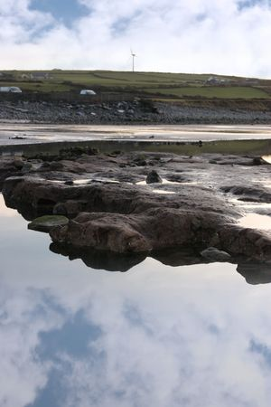 rock pool on beale beach co kerry ireland on a cold winters morning with turbine in the background photo