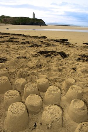 sandcastles: childrens sandcastles on a beach in ireland with cliffs and real castle in background Stock Photo