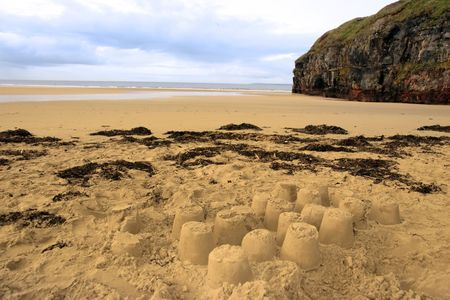 sandcastles: childrens sandcastles on a beach in ireland with cliffs in background