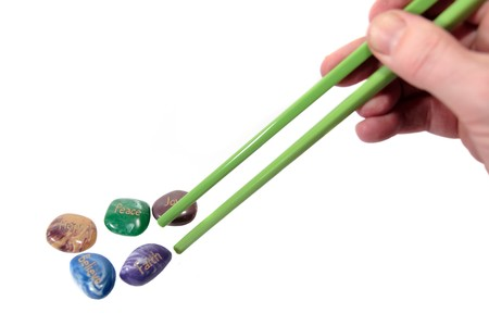 inscribed: five stones inscribed hope joy peace faith and believe being picked up by chopsticks showing have belief