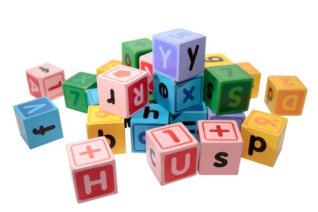 assorted childrens toy letter building blocks against a white background Stock Photo