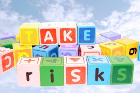 assorted childrens toy letter building blocks against a cloudy background that spell take risks Stock Photo - 7390357