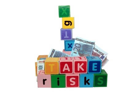 assorted childrens toy letter building blocks against a white background that spell take risks photo
