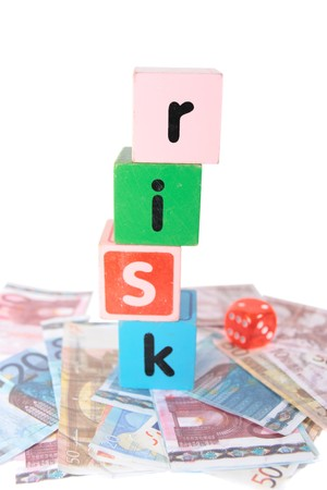 assorted childrens toy letter building blocks and dice against a white background on money that spell risk photo