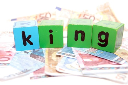 assorted childrens toy letter building blocks against a white background on money that spell king photo