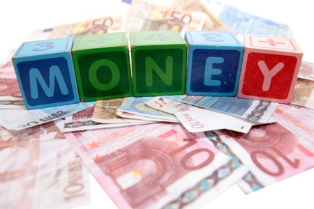 assorted childrens toy letter building blocks against a white background on money that spell money photo