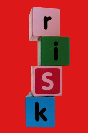 assorted childrens toy letter building blocks against a red background that spell risk photo
