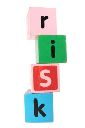 assorted childrens toy letter building blocks against a white background that spell risk photo