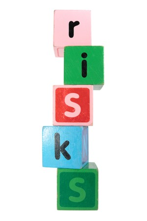 assorted childrens toy letter building blocks against a white background that spell risks photo