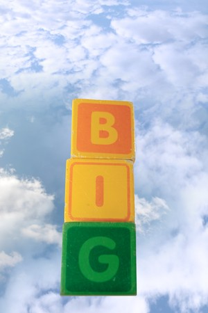 childrens toy letter building blocks against a cloudy background spelling big with copy space photo