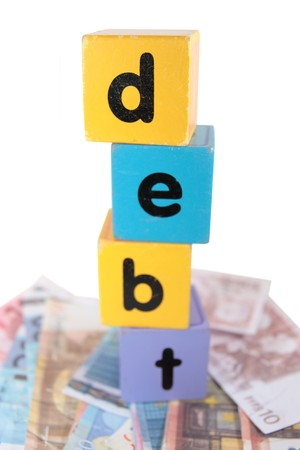 assorted childrens toy letter building blocks against a white background on money that spell debt photo