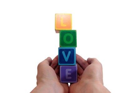 childrens toy letters in outstretched hands  against a white background that spell love photo