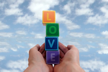 childrens toy letters in outstretched hands against cloudy background, photo