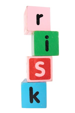 risk spelt with childrens toy letter building blocks against a white background  photo
