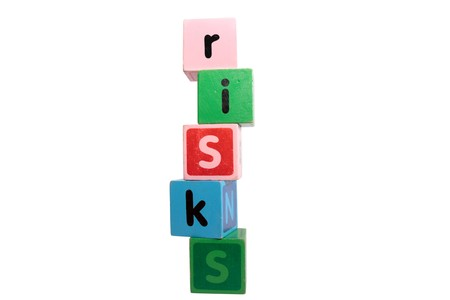 risks spelt with childrens toy letter building blocks against a white background  photo