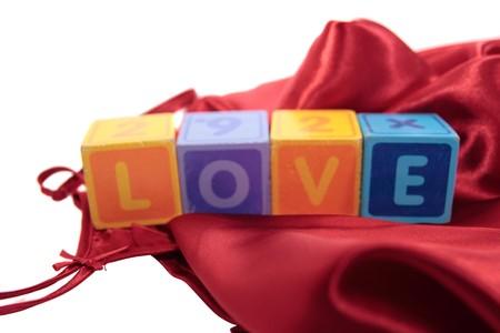 silky lingerie: love written with blocks on a silk nightie against white background