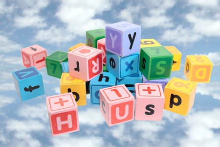 assorted childrens toy letter building blocks against a cloudy background Stock Photo - 7534075